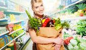 Kvinna shopping för frukt och grönsaker i råvaror institutionen — Stockfoto