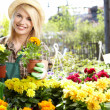 Garden center worker smiling and holding up yellow flower  — Stock Photo