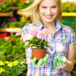 Woman shopping for and looking at plants in garden center — Stock Photo