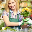 Stock Photo: Woman holding a flower box while smiling