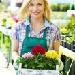 Woman holding a flower box while smiling - Stock Photo