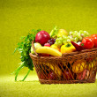 Basket full of fresh produce. green background - Foto Stock