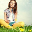 Beautiful girl lies on meadow and reads the boo — 图库照片