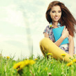 Beautiful girl lies on meadow and reads the boo — Stok fotoğraf