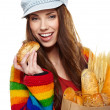 Young woman holding a grocery bag full of bread  — Stock fotografie