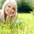 Beautiful young woman on field in summer — Stock Photo #25997049