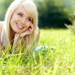Beautiful young woman on field in summer — Stock Photo