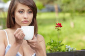 Portrait of cute teenage girl with cup of coffee on the terrace — Stock Photo