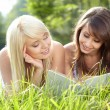 Two young beautiful girls reading book at summer green park  — Foto Stock