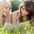 Two young beautiful girls reading book at summer green park  — Stok fotoğraf