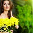 Young happy girl in yellow flowers, outdoor photo session  — Stock Photo