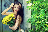 Happy smiling young woman with flower bouquet — Stock Photo