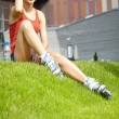 Woman skating in city. Girl going rollerblading sitting in grass — Stock Photo #26551139