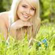 Beautiful young woman relaxing in the grass — Stock Photo #26551435