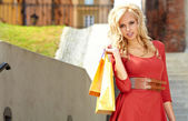 Blondýnka s mnoha malých nákupní tašky — Stock fotografie