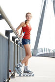 Beautiful girl rollerskating in morning city — Stock Photo