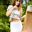 Stock Photo: Pretty woman is painting. Open air session.