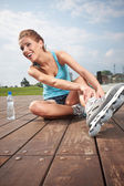 Roller girl resting on the steps — Stock Photo