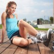 Young woman putting on skates going rollerblading — Stock Photo #26862005