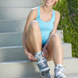 Young woman putting on skates going rollerblading — Stock Photo #26862205
