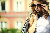 Fashionable girl in white dress with shopping bag — Stock Photo