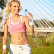 Cheerful young attractive woman drinking water, outdoors — Stock Photo #27300693