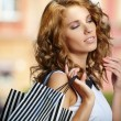 Fashionable girl in white dress with shopping bag — Stok fotoğraf