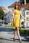 Fashionable girl in yellow dress with shopping bag — Stock Photo