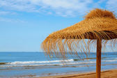 Tropical beach scenery with parasol — Stock Photo