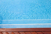 Fragment of a swimming pool and wooden floor — Stock Photo
