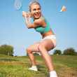 Fitness, young woman playing badminton in a city park — Stock Photo #28187813