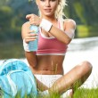 Stock Photo: Thirsty sporty woman drinking water after training