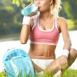 Thirsty sporty woman drinking water after training — Stock Photo