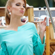 Elegant retro woman wear dress , sitting near the wooden yacht. — Foto de Stock