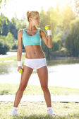 Fitness instructor exercising with small weights in green park — Stock Photo