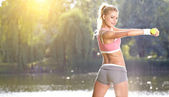 Female fitness instructor exercising with small weights — Stock Photo