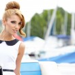 Attractive fashion girl on the dock with boat — Stock Photo #28198583