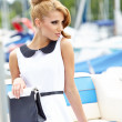 Attractive fashion girl on the dock with boat — Stock Photo #28198659