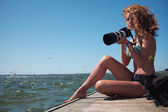 Summer girl on the bridge photographing surfers — Stock Photo