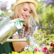 Smiling young woman watering flowers in the flowers market — Stock Photo