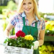 Florists woman working with flowers at a greenhouse. — Stockfoto