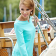 Elegant retro woman wear dress , sitting near the wooden yacht. — Stock Photo