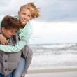Couple running on beach holding hands smiling — Stock Photo