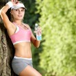 Young attractive fitness woman drinking water, outdoors — Stock Photo #29095595
