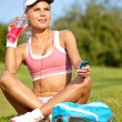 Woman in pink sports bra rests holding a water bottle — Stock Photo #29096623