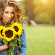 Young fashion woman with a bouquet of sunflowers in the field — Stock Photo #29336119
