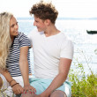 Young beautiful couple in love sitting near the water  — Stock Photo