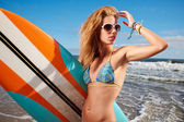 Surfer girl on the beach — Stock Photo