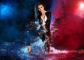 Bela garota sexy com arma na água. fundo de fumo — Fotografia Stock
