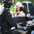 Sexy girl in car looking a man on a motorcycle — Stock Photo